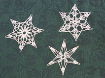 Crocheted snowflakes. On green holly-patterned fabric background Stock Photo