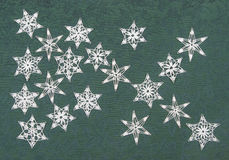 Crocheted snowflakes. On green holly-patterned fabric background Royalty Free Stock Image