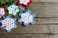 Crocheted snowflakes, two hooks on an old wooden background with blank copy space for text. Simple winter crafts for kids Royalty Free Stock Photo