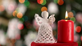 Crocheted xmas angel and burning candle on blurry christmas tree background stock footage