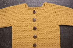 Crocheted yellow cardigan on a black background stock photo