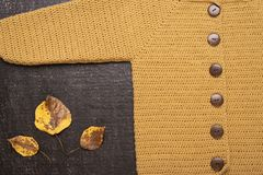 Crocheted yellow cardigan on a black background royalty free stock photography