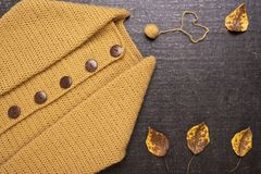Crocheted yellow cardigan on a black background royalty free stock images