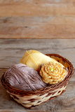 Crocheted yellow rose with brown leaves and two skeins of cotton yarn in a basket. Beautiful knitted flower adorned with beads Stock Photo