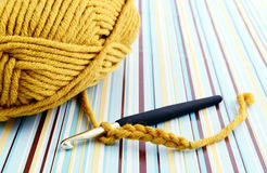 Crocheting with brown wool Stock Images