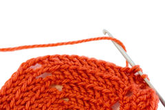 Crocheting double stitch. Double crochet stitch using crochet hook and orange wool Royalty Free Stock Photo