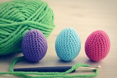 Crocheting easter eggs with blue pink green. wooden table backgr Royalty Free Stock Photo
