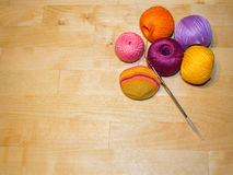 crocheting in progress and colorful cotton thread balls on the wooden background with space Royalty Free Stock Photo