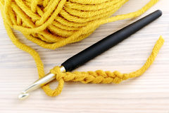 Crocheting with yellow wool on table Stock Photo