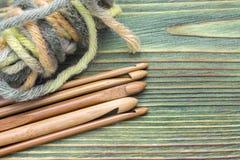 Crochets de crochet et boule en bambou naturels en bois de fil sur la table verte Lieu de travail créatif pour les métiers faits  Photographie stock