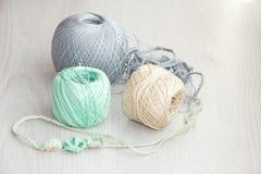 Crochets de crochet et boules de fil sur le fond en bois Image stock