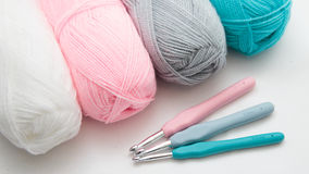 Crochets and hooks. Color crochets and three crochet hooks on white table Stock Photos