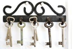 Crochets métalliques de vintage accrochant de vieilles clés sur le fond blanc Photographie stock libre de droits