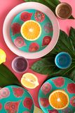 Crockery pattern. Cups and plates near tropical leaves and fruits on pink background top view Stock Photography