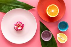 Crockery pattern. Cups and plates near tropical leaves and fruits on pink background top view Stock Photo