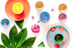 Crockery pattern. Cups and plates near tropical leaves and fruits on white background top view Royalty Free Stock Photos