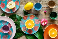 Crockery pattern. Cups and plates near tropical leaves and fruits on wooden background top view Stock Image