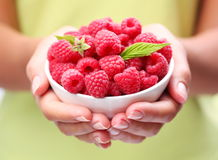 Crockery with raspberries. Crockery with raspberries in woman hands Royalty Free Stock Photography