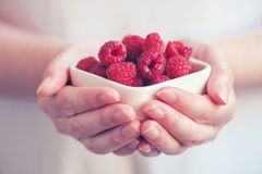 Crockery with raspberries in woman hands. Selective focus Royalty Free Stock Photo