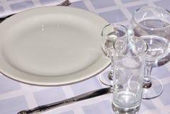 crockery Vidros de vidro, vidros de vinho, vidros, placas que estão em uma toalha de mesa branca e brilho claro refletindo imagem de stock