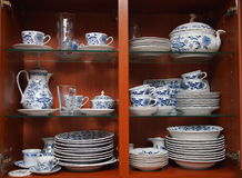 Crockery in wooden kitchen cabinet. Mugs, cups and plates with blue and white pattern of flowers and onions. All neatly cleaned up in a wooden kitchen cabinet stock photos