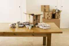 Crockery wrapped in paper beside cardboard box on dining room table, sealed boxes in background Stock Photos