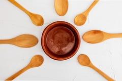 Crockpot et cuill?res en bois sur le fond blanc avec la texture L'espace pour ins?rer votre texte ici Lettre pour des restaurants photo stock