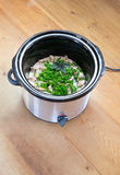 Crockpot slow cooker meal with chicken and fresh herbs. On a scratched wooden kitchen benchtop Stock Photos