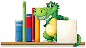 A crocodile above the shelf holding an empty signboard Stock Photos