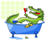 Crocodile in a bathtub. The green, smiling crocodile lies in a bathtub and holds a toothbrush and a tube with a toothpaste Stock Photography