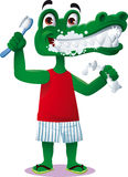 Crocodile dental care. A crocodile smiles while brushing your teeth with toothpaste Royalty Free Stock Photography