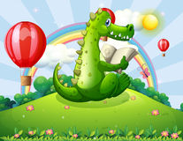 A crocodile reading at the hilltop with a rainbow Royalty Free Stock Photography