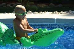 Crocodile ride. Six years old boy playing in the pool Stock Photo