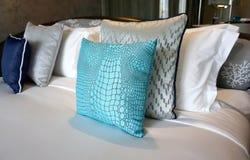 Crocodile skin blue fabric cushion. On the white bed royalty free stock photo