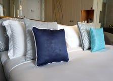 Crocodile skin blue fabric cushion. On the white bed stock photos