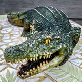 Crocodile Statue on a Mosaic Leaf Table. A crocodile statue with a toothy grin on a mosaic leaf table royalty free stock photography