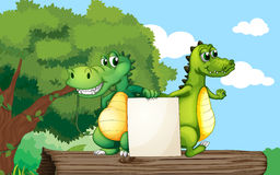 Crocodiles at the top of a trunk holding an empty board Royalty Free Stock Photos