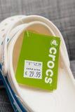 Crocs堵塞鞋子在灰色背景的购物袋 库存照片