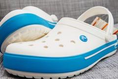 Crocs堵塞鞋子在灰色背景的购物袋 图库摄影