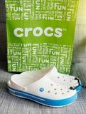 Crocs堵塞鞋子在灰色背景的购物袋 免版税图库摄影