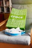Crocs堵塞鞋子在灰色背景的购物袋 免版税库存图片