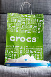 Crocs堵塞鞋子在灰色背景的购物袋 库存图片