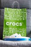Crocs закупоривает хозяйственную сумку ботинок на серой предпосылке Стоковые Изображения
