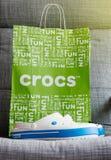 Crocs zatyka buta torba na zakupy na szarym tle Zdjęcie Stock