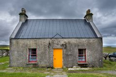 The croft house whitehouse, with orange door and dark red windows, on a stormy, cloudy day royalty free stock photography