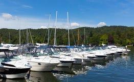 Crogioli di cabinato in una fila su un lago con bello cielo blu di estate Immagini Stock Libere da Diritti