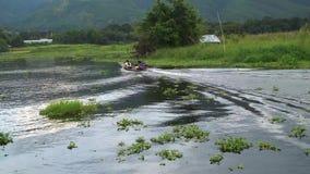 Crogiolo di guida di A lungo coda della gente locale birmana nel lago Inle stock footage