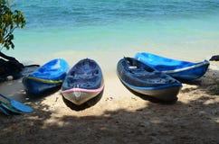 Crogiolo di kajak sulla spiaggia con il mare blu, sotto ombreggiato Fotografia Stock