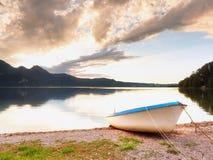 Crogiolo di pagaia bianco abbandonato sulla banca del lago alps Lago evening Immagine Stock