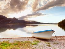 Crogiolo di pagaia bianco abbandonato sulla banca del lago alps Lago evening Fotografia Stock Libera da Diritti